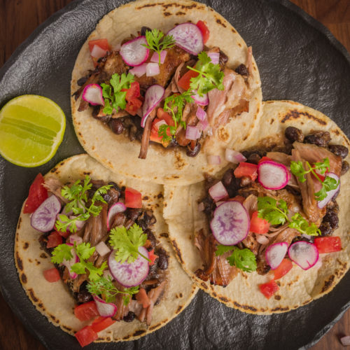 Carnitas tacos with refried beans, tomato, onion, coriander